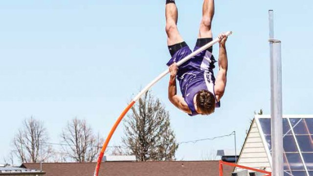 Garrett Schwindt makes for the high bar at Pine Bluffs during the Southeast Athletic Conference meet on Saturday.
