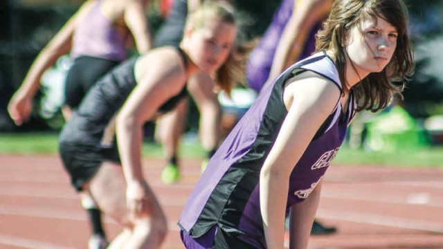 Brook Eldred and the rest of the 2A girls' 4x100 field watch intently while waiting impatiently for the relay runner to reach their position, the third leg of the race. Passing the baton between two runners traveling at full speed requires incredible coordination and timing.